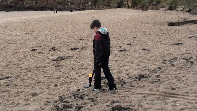 Kid Metal Detecting on Beach